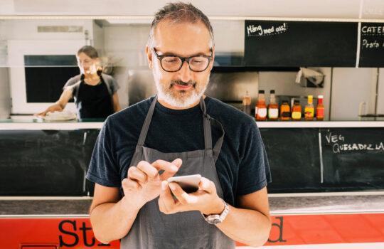 A man using his phone in a food van.