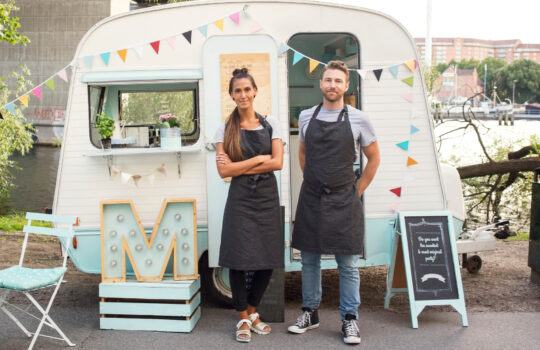 Two business owners stood in front of a converted caravan.