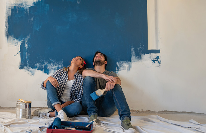 A couple painting a blue wall